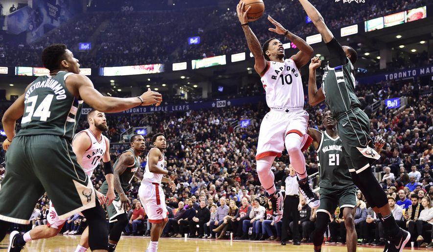 Toronto Raptors guard DeMar DeRozan (10) shoots over Milwaukee Bucks forward John Henson (31) during first half NBA basketball action in Toronto on Monday, Jan. 1, 2018. (Frank Gunn/The Canadian Press via AP)