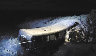 This early Monday, Jan. 1, 2018, photo released by Utah Department of Public Safety shows the scene of a Greyhound bus crash in rural Green River, Utah, Authorities are investigating the bus crash that killed a 13-year-old girl and injured at least 11 others. Utah's Highway Patrol says the bus headed to Las Vegas crashed Sunday night off Interstate 70 west of the Utah city of Green River. The bus went off the highway shoulder into a steep wash and stopped about 200 feet away from the road. The bus driver and two passengers were airlifted in serious condition to hospitals in Colorado and Utah. Eight others were also hospitalized. (Utah Department of Public Safety via AP)