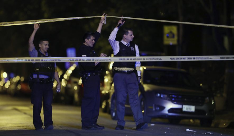 FILE - In this Sept. 2, 2017, file photo, police lift crime scene tape after two people were shot and transported to Stroger Hospital in Chicago. Chicago ended 2017 with fewer homicides than the year before but raging gang wars in the city's most violent neighborhoods drove the total beyond the 600 mark for just the second time in well over a decade. (John J. Kim/Chicago Tribune via AP, File)