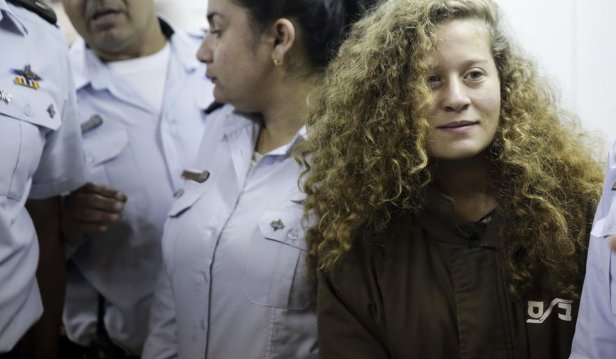 File - In this Thursday, Dec. 28, 2017 file photo, Ahed Tamimi is brought to a courtroom inside Ofer military prison near Jerusalem. Tamimi, 16, from the village of Nebi Saleh on Monday for attacking the soldiers as well as for previous altercations. It extended her remand for 8 days. (AP Photo/Mahmoud Illean, File)