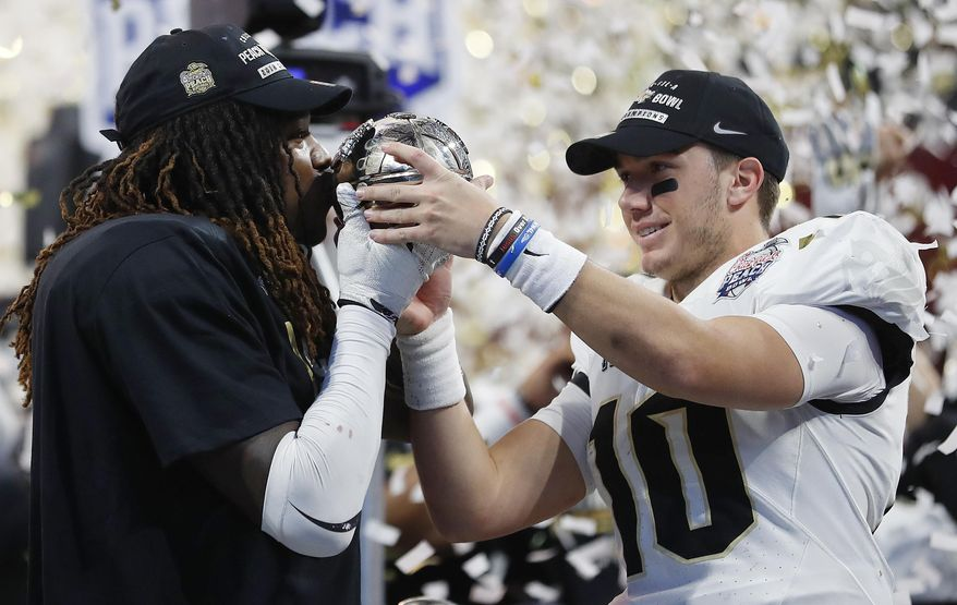 Central Florida linebacker Shaquem Griffin, left, kisses the championship trophy as Central Florida quarterback McKenzie Milton looks on after the Peach Bowl NCAA college football game against Auburn, Monday, Jan. 1, 2018, in Atlanta. Central Florida won 34-27. (AP Photo/John Bazemore)