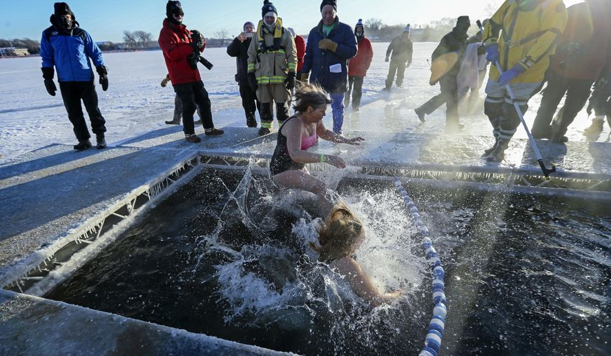 Hundreds brave the sub zero temperatures on New Years Day morning to take a frigid leap into the icy waters of Lake Minnetonka, Monday, Jan. 1, 2018. It was the annual ALARC ICE DIVE at the Port of Excelsior dock, to help raise money for US veterans. (Brian Peterson/Star Tribune via AP)