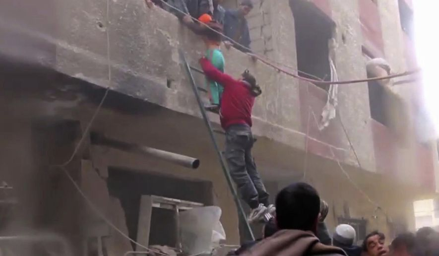 In this frame grab from video released Monday Jan. 1, 2018 by the Syrian Civil Defense group, known as the White Helmets, Syrians evacuate a boy from a building by using a ladder after an airstrike hit the Damascus suburb of Masraba, Syria. Opposition activists are reporting heavy clashes between government forces and insurgents east of Damascus, and at least a dozen airstrikes. (Syrian Civil Defense, via AP)