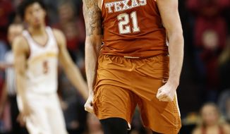Texas forward Dylan Osetkowski celebrates after making 3-point basket at the end of an NCAA college basketball game against Iowa State, Monday, Jan. 1, 2018, in Ames, Iowa. Texas won 74-70 in overtime. (AP Photo/Charlie Neibergall)