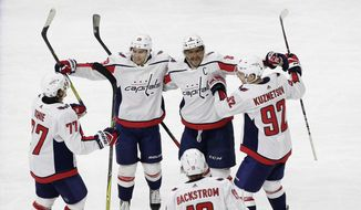 Washington Capitals' Alex Ovechkin (8), of Russia, is congratulated by Evgeny Kuznetsov (92), of Russia; Nicklas Backstrom (19), of Sweden; T.J. Oshie (77); and Christian Djoos (29) following Ovechkin's overtime goal in an NHL hockey game against the Carolina Hurricanes in Raleigh, N.C., Tuesday, Jan. 2, 2018. Washington won 5-4. (AP Photo/Gerry Broome)
