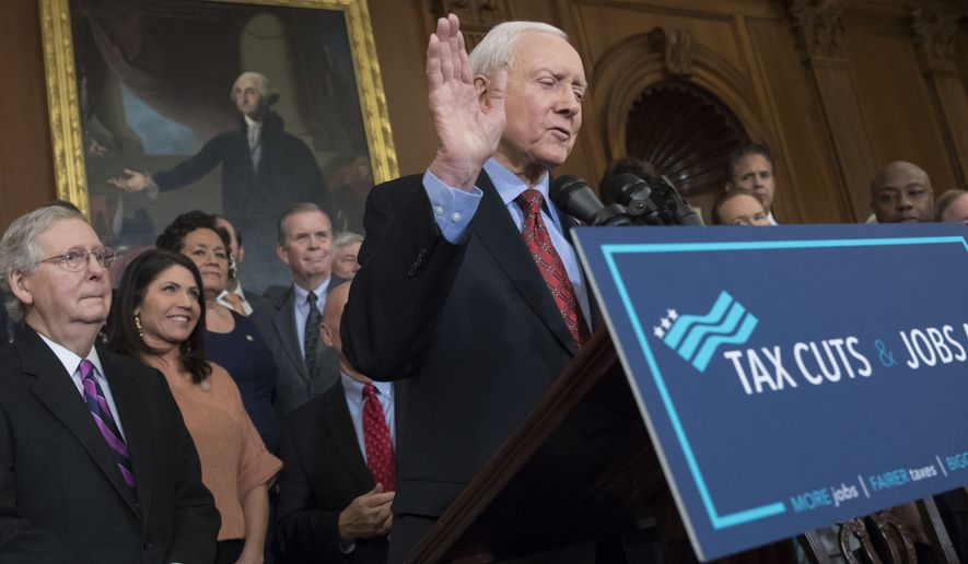 FILE - In this Dec. 21, 2017, file photo, Sen. Orrin Hatch, R-Utah, chairman of the Senate Finance Committee, is joined at left by Senate Majority Leader Mitch McConnell, R-Ky., waves as he concludes his remarks and prepares to sign the final version of the GOP tax bill, at the Capitol in Washington. Hatch, 83, says he is retiring after four decades in Senate. (AP Photo/J. Scott Applewhite, File)