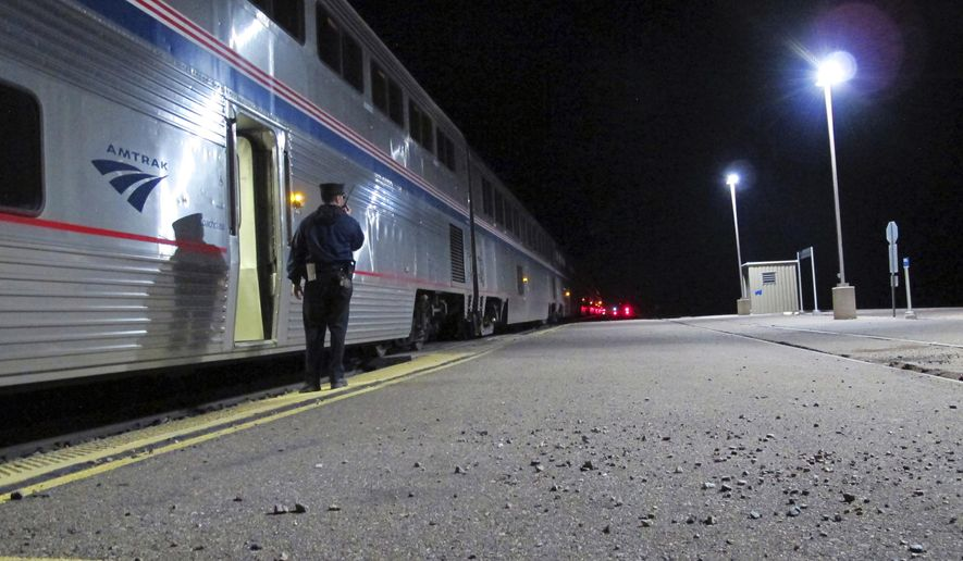 In this Friday, Dec. 29, 2017 photo, an Amtrak employee signals that all passengers are clear as the train departs the Williams Junction station outside Williams, Ariz. Service at the Williams Junction station ended Monday, Jan. 1, 2018. Passengers now are dropped off and picked up in downtown Flagstaff.  (AP Photo/Felicia Fonseca)