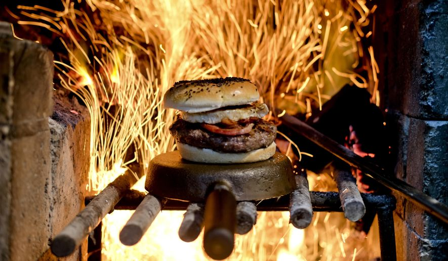 In this Nov. 11, 2017 photo, a hamburger sits for display before a wood-fueled fire at Kon Kon restaurant in Buenos Aires, Argentina. Argentine cuisine has long been known worldwide for its barbecued beef, but chefs there are now taking the country's passion for grilling with wood to a new level and earning international recognition by experimenting with new dishes in open-fire ovens, including fast food. (AP Photo/Luis Henao)