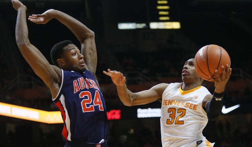 Tennessee guard Chris Darrington (32) is defended under the basket by Auburn forward Anfernee McLemore (24) in the first half of an NCAA college basketball game Tuesday, Jan. 2, 2018, in Knoxville, Tenn. (AP Photo/Crystal LoGiudice)