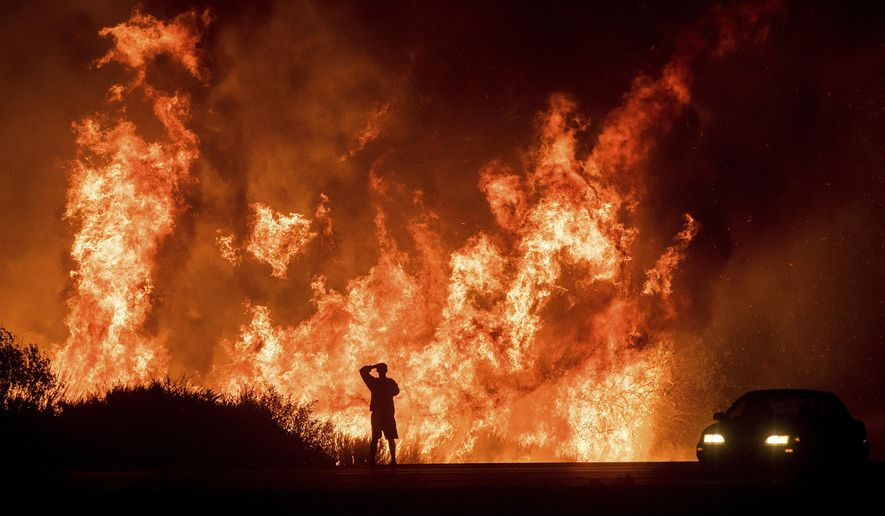 FILE - In this Dec. 6, 2017, file photo, a motorists on Highway 101 watches flames from the Thomas fire leap above the roadway north of Ventura, Calif. President Donald Trump has declared a major disaster in California over a wildfire that destroyed more than 1,000 buildings. The White House announced Tuesday, Jan. 2, 2018, that the president has granted disaster status, which will help make federal funds available to supplement recovery efforts in the wake of the Thomas Fire that ravaged Santa Barbara and Ventura counties. (AP Photo/Noah Berger, File)