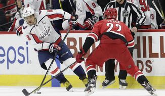 Washington Capitals' Alex Ovechkin (8), of Russia, controls the puck while Carolina Hurricanes' Brett Pesce (22) defends during the first period of an NHL hockey game in Raleigh, N.C., Tuesday, Jan. 2, 2018. (AP Photo/Gerry Broome)