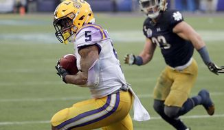 LSU running back Derrius Guice (5) makes a reception to score a touchdown in front of Notre Dame linebacker Drue Tranquill  during the second half of the Citrus Bowl NCAA college football game, Monday, Jan. 1, 2018, in Orlando, Fla. Notre Dame won 21-17. (AP Photo/John Raoux)