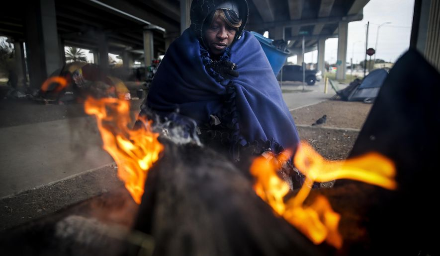 Tony Sampson, who received a blanket from Star of Hope's Love in Action van, tries to warm up by a fire under the Eastex Freeway as temperatures hover in the 30s Tuesday, Jan. 2, 2018 in Houston.  Plunging overnight temperatures in Texas brought rare snow flurries as far south as Austin, and accidents racked up on icy roads across the state. In the central Texas city of Abilene, the local police chief said more than three dozen vehicle crashes were reported in 24 hours. (Michael Ciaglo/Houston Chronicle via AP)
