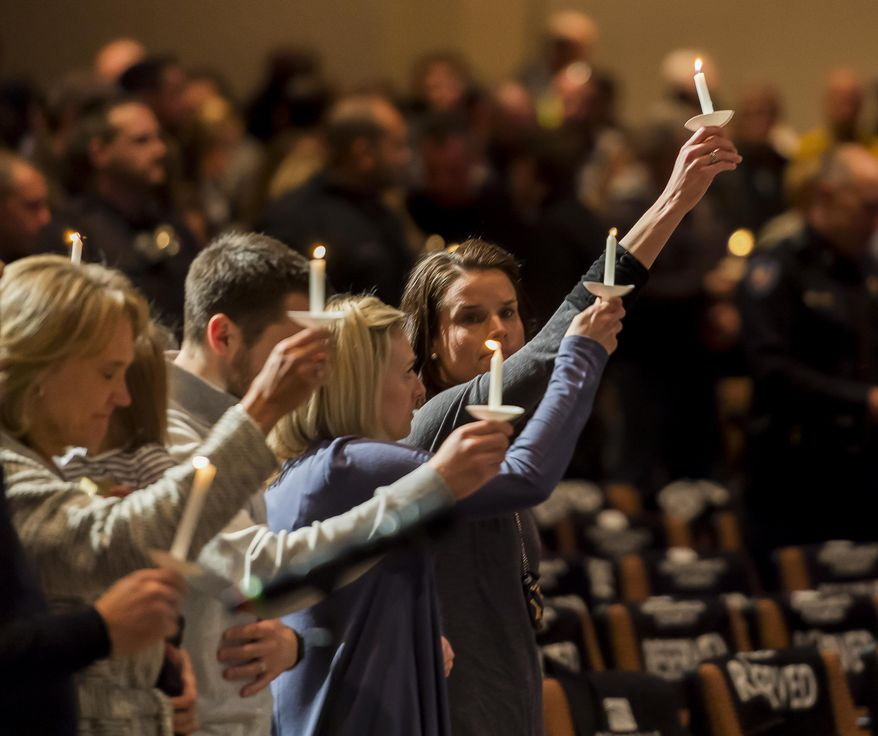 Gracie Parrish, center, holds a candle for her late husband Zackari Parrish, a Douglas County deputy, at Mission Hills Church in Littleton, Colo., Monday, Jan. 1, 2018. A man who shot and killed the Colorado deputy and wounded several others along with a few civilians was an attorney and an Iraq war veteran who had posted videos online in recent months criticizing professors and law enforcement officials, authorities said Monday. (Dougal Brownlie/The Gazette via AP)