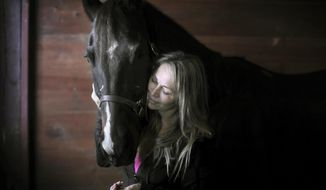 In a Dec. 5, 2017 photo, Tori Sue Olson shares a moment with her horse, Flit the Leader, while inside the stable where she boards him near Palmyra, Wis. Olson, who overcame a cocaine addiction and the loss of a close, father-like friend, nursed her horse Leader back to health after a life-threatening pelvic injury to become a National Barrel Horse Association World Championships finalist.  (Anthony Wahl/The Janesville Gazette via AP)