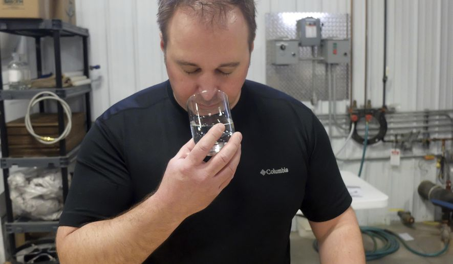 In a Dec. 18, 2017 photo, Mike Swanson inhales the scent from raw distillate at Far North Spirits, in Hallock, Minn. He said different rye varieties often have strikingly different tastes when distilled. Swanson added that this is the first public research into the flavor characteristics of grain alcohol. Swanson, who owns Hallock, Minn.-based Far North Spirits, argues craft distillers need to pay more attention to the front end of the process.  (Dan Gunderson/Minnesota Public Radio via AP)