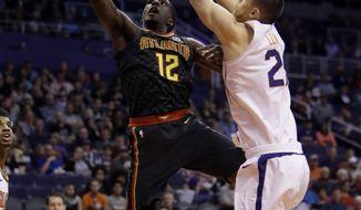 Atlanta Hawks forward Taurean Prince (12) drives past Phoenix Suns center Alex Len in the first half during an NBA basketball game, Tuesday, Jan. 2, 2018, in Phoenix. (AP Photo/Rick Scuteri)
