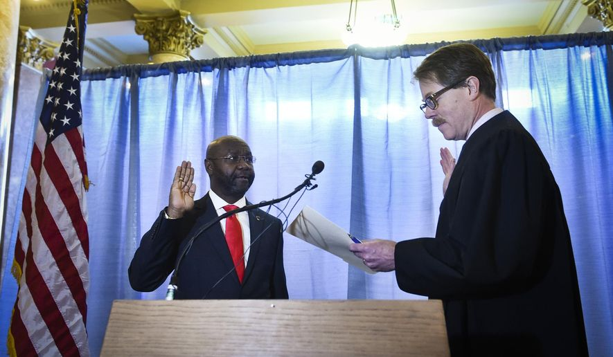 Helana's new Mayor Wilmot Collins, left, is sworn into office by Judge Mike Menahan, Tuesday morning, Jan. 2, 2018, in the Capitol Rotunda in Helena, Mont. Collins is a Liberian refugee who was elected mayor of Helena in November. (Thom Bridge/Independent Record via AP)