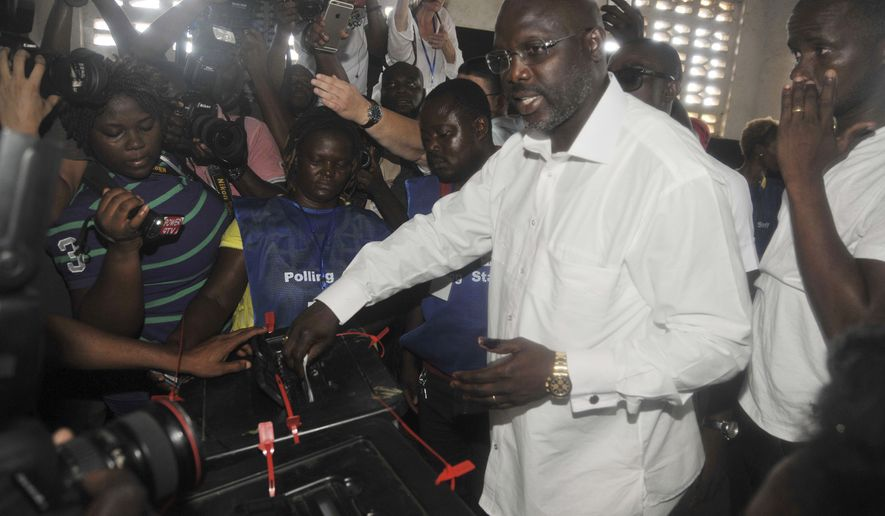FILE - In this Oct. 10, 2017, file photo, former soccer star George Weah, presidential candidate for the Coalition for Democratic Change, casts his vote during the presidential election in Monrovia, Liberia.  Raised in a poor neighborhood on the neglected outskirts of the capital Monrovia, Weah was elected president of his country last week, his victory a lesson in how sports fame can help propel figures with humble beginnings to positions of great importance. (AP Photo/Abbas Dulleh, File)