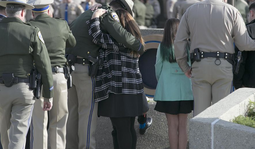 FILE - In this Dec. 27, 2017 file photo, Rosanna Camilleri, right, the wife of late California Highway Patrol Officer Andrew Camilleri Sr., hugs CHP officer Jonathan Velazquez following a bell ringing ceremony held at the highway patrol academy in West Sacramento, Calif. Authorities say a 22-year-old man who killed Camilleri Sr. on Christmas Eve after he slammed his car into the back of the officer's parked patrol car has been charged with second-degree murder. Alameda County District Attorney Nancy O'Malley on Tuesday, Jan. 2, 2018, identified Mohammed Ali, of Hayward, as the driver of a speeding Cadillac that drifted off Interstate 880 and crashed against Officer Andrew Camilleri's patrol SUV. (AP Photo/Rich Pedroncelli, File)