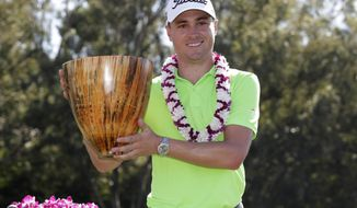 FILE - In this Jan. 8, 2017, file photo, Justin Thomas holds the champions trophy after the final round of the Tournament of Champions golf event at Kapalua Plantation Course in Kapalua, Hawaii. Thomas is one of only nine players who make it back to Kapalua this year. (AP Photo/Matt York, File)