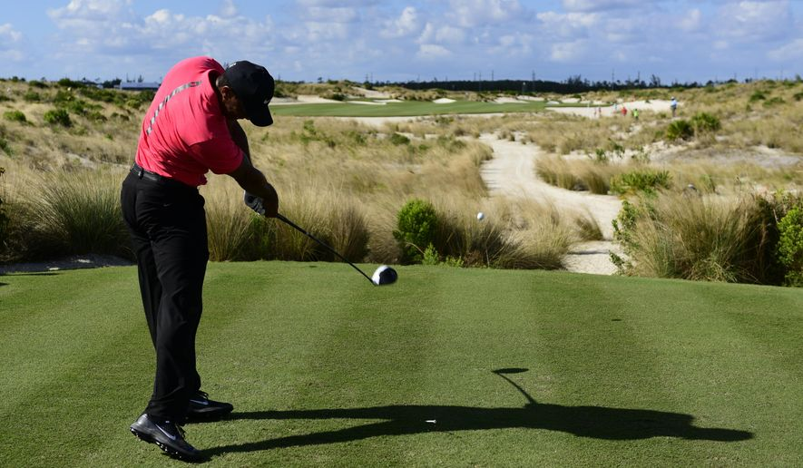 FILE - In this Dec. 3, 2017, file photo, Tiger Woods tees off from the 14th hole during the final round of the Hero World Challenge golf tournament at Albany Golf Club in Nassau, Bahamas. How Woods fares this year is one of the top story lines for 2018. (AP Photo/Dante Carrer, File)