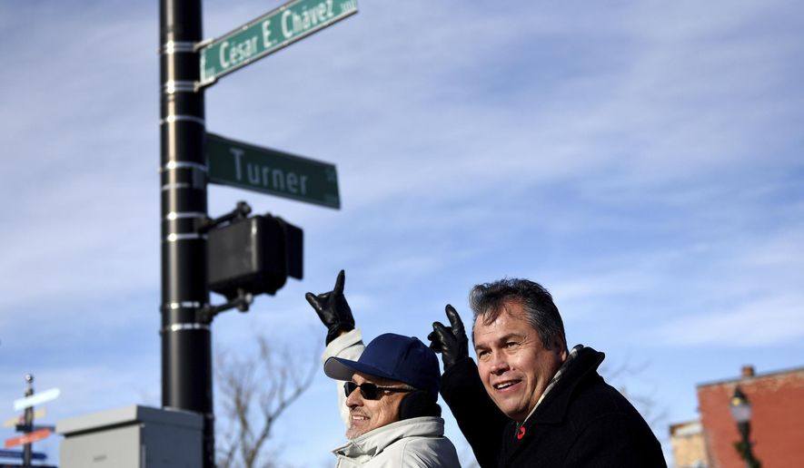 Guillermo Lopez, left, and Andy Garza point to the Cesar E. Chavez Avenue sign while posing for a photograph during an unveiling ceremony to mark the changing of Grand River Avenue to Cesar E. Chavez Avenue on Tuesday, Jan. 2, 2018, at the intersection of Cesar E. Chavez Avenue and Turner Street in Old Town Lansing, Mich.  (Nick King/Lansing State Journal via AP)