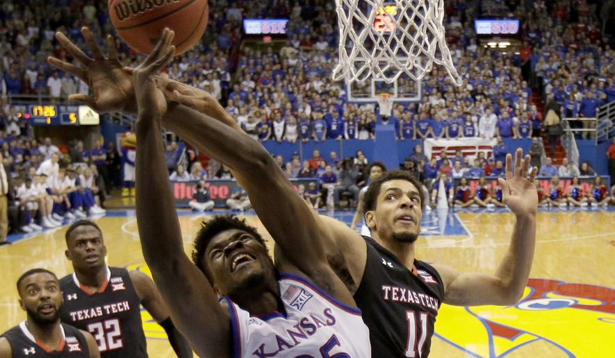 Kansas' Udoka Azubuike (35) is fouled by Texas Tech's Zach Smith (11) as he shoots during the first half of an NCAA college basketball game Tuesday, Jan. 2, 2018, in Lawrence, Kan. (AP Photo/Charlie Riedel)