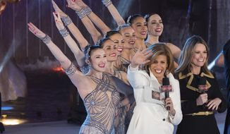 """FILE - In this Nov. 29, 2017, file photo, Savannah Guthrie, right, and Hoda Kotb appear with the Rockettes during the 85th annual Rockefeller Center Christmas Tree lighting ceremony in New York. NBC News opened the new year by appointing Kotb as co-anchor of the """"Today"""" show's first two hours with Guthrie, replacing Matt Lauer following his firing on sexual misconduct charges in late November.  (Photo by Charles Sykes/Invision/AP, File)"""