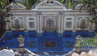 In this Tuesday, Dec. 26, 2017, photo, Joey Cargill of Manila, from the Philippines, left, and David Tamuty of Fort Lauderdale, Fla., lounge in the swimming pool lined with 24-karat gold tiles at The Villa Casa Casuarina in Miami Beach, Fla., as seen from the hotel's rooftop deck. The boutique hotel was once the home of slain fashion designer Gianni Versace. (AP Photo/Jennifer Kay)