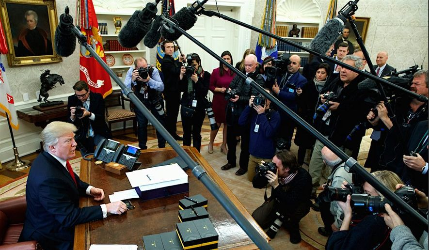 President Trump has a moment with reporters and photographers in the Oval Office of the White House. (AP Photo/Evan Vucci) (Associated Press) ** FILE **