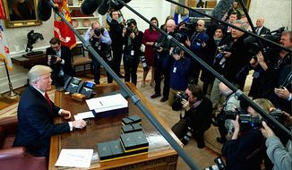 President Trump has a moment with reporters and photographers in the Oval Office of the White House. (AP Photo/Evan Vucci) (Associated Press) **FILE**