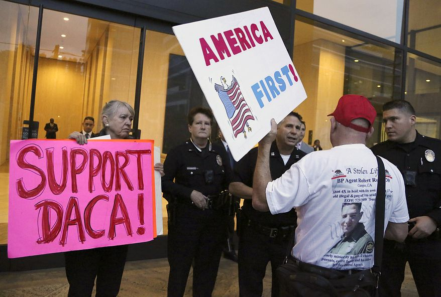 A supporter of President Donald Trump challenges police officers and a Deferred Action for Childhood Arrivals (DACA) program during a rally outside the office of California Democratic Sen. Dianne Feinstein in Los Angeles, Wednesday, Jan. 3, 2018. (AP Photo/Reed Saxon) ** FILE **