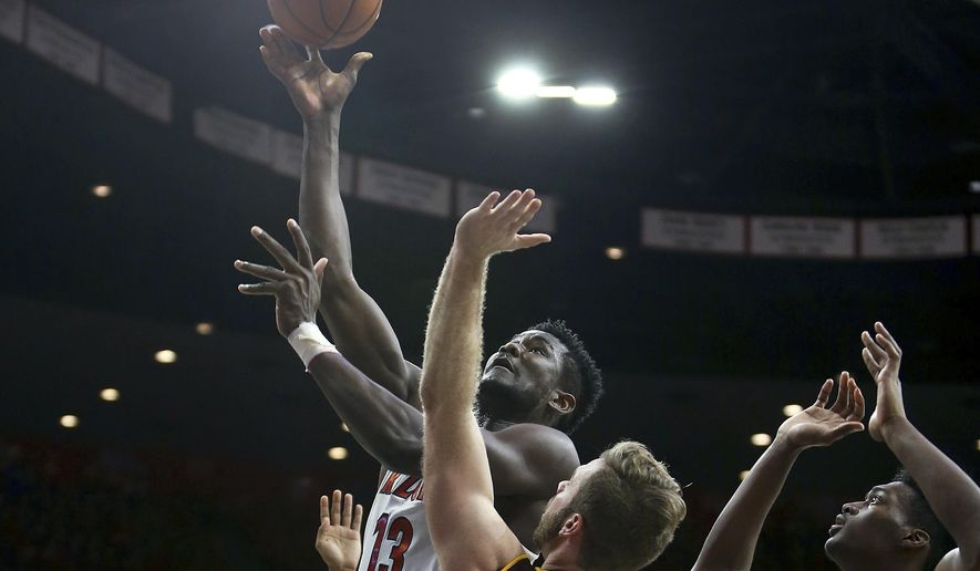 Arizona forward Deandre Ayton (13) shoots over Arizona State's Mickey Mitchell, center, and DeQuon Lake during the second half of an NCAA college basketball game Saturday, Dec. 30, 2017, in Tucson, Ariz. (AP Photo/Ralph Freso)