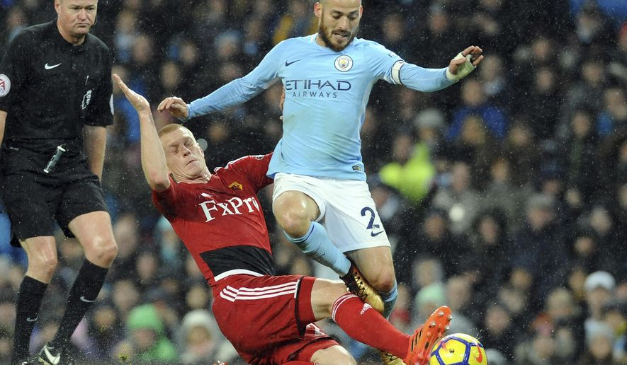 Manchester City's David Silva, right, vies for the ball with Watford's Ben Watson during the English Premier League soccer match between Manchester City and Watford at Etihad stadium, in Manchester, England, Tuesday, Jan. 2, 2018. (AP Photo/Rui Vieira)