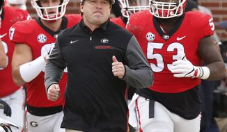 FILE - In this Nov. 25, 2017, file photo, Georgia head coach Kirby Smart leads his team onto the field before the start of a NCAA college football game against Georgia Tech, in Atlanta. Alabama and Georgia don't play as often as many would think so when the teams meet it's special, even when it is a regular season matchup. But when the Crimson Tide and Bulldogs meet Monday night, Jan. 8, 2018, in Atlanta it will be an event. The teams, which routinely play each other just four times a decade, will be playing for the College Football Playoff national championship. (Joshua L. Jones/Athens Banner-Herald via AP, File)