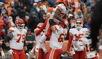 Kansas City Chiefs running back Kareem Hunt, top, is lifted by teammate Jordan Devey after Hunt's rushing touchdown against the Denver Broncos during the first half of an NFL football game Sunday, Dec. 31, 2017, in Denver. (AP Photo/Jack Dempsey)