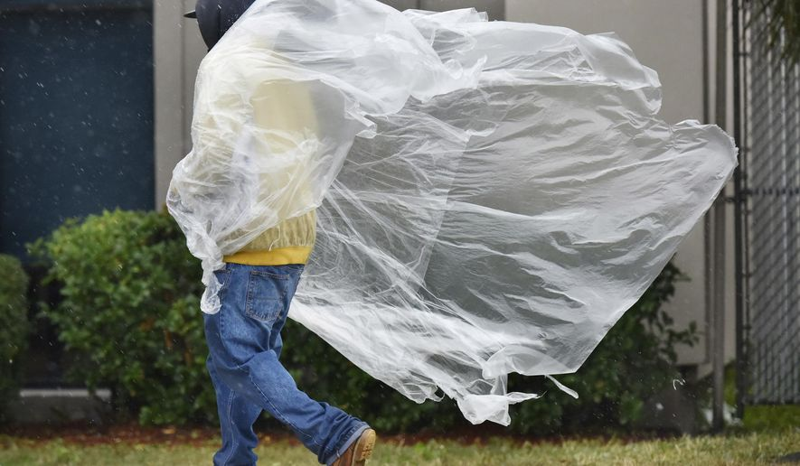A pedestrian's makeshift raincoat blows in the rainy cold weather Wednesday, Jan. 3, 2018, along Philips Highway in Jacksonville, Fla. A hard freeze with possible icy roads is predicted overnight. (Will Dickey/The Florida Times-Union via AP)