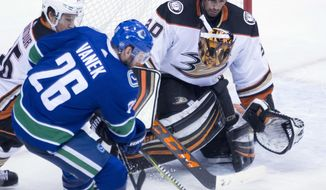 Anaheim Ducks goaltender Ryan Miller's mask falls off as Vancouver Canucks left wing Thomas Vanek (26) tries to get a shot on net during the third period of an NHL hockey game Tuesday, Jan. 2, 2018, in Vancouver, British Columbia. (Jonathan Hayward/The Canadian Press via AP)