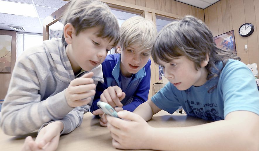 ADVANCE FOR RELEASE MONDAY, JANUARY 8, 2018 Lincoln Elementary School fifth-graders, Fifth grade students at Lincoln Elementary School in Madison, Wis. including from left, Simon Yuroff, Gus Tills and Lucero Dunscombe, pictured Monday, Dec. 11, 2017, use a mobile phone to view a digital rendering of a children's book about the Ho-Chunk Nation which they helped write and illustrate as third-graders at the school. A tribal grant printed 2,000 copies of the book, which the students will see finished for the first time at a book release party at the school on Friday, Jan. 5, 2017. (John Hart/Wisconsin State Journal via AP)