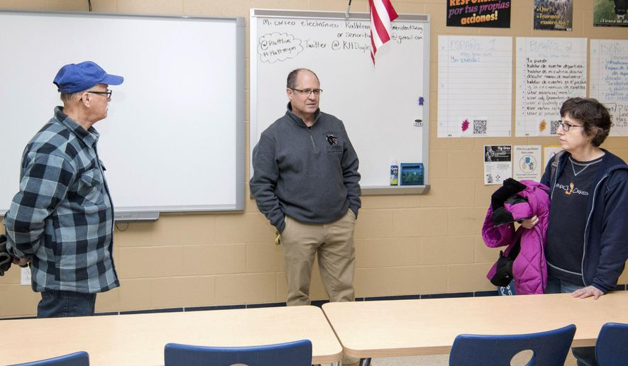 In this Saturday, Dec. 30, 2017 photo, Platt High School Principal Robert Montemurro, center, leads a tour through a Spanish classroom for its Open House and Tour in Meriden, Conn. Marveling at the newly installed electronics and towering windows, parents and alumni from as far back as the 1960s were re-introduced to the new Meriden high schools by students and staff on Saturday. (Devin Leith-Yessian/Record-Journal via AP)