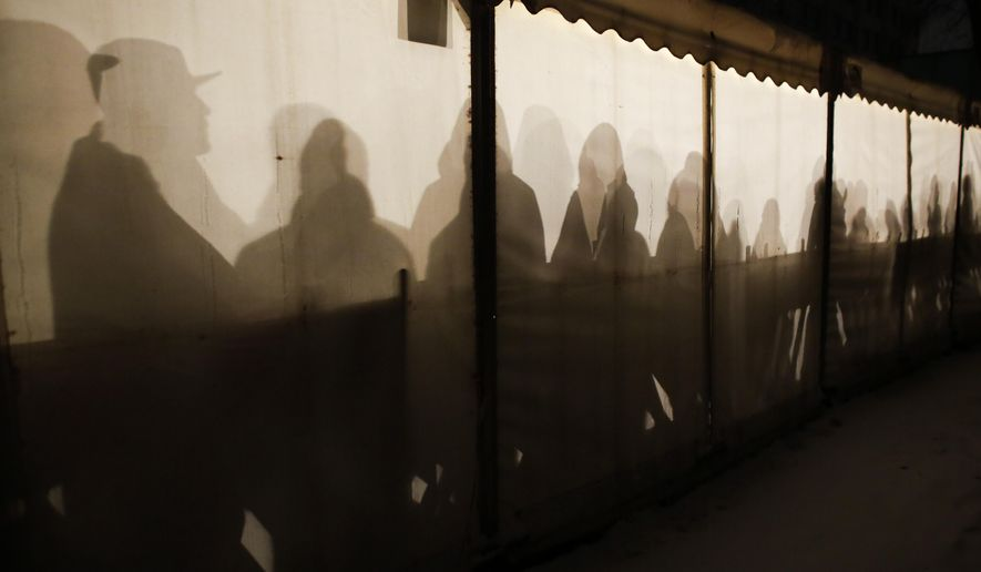 FILE - In this Jan. 6, 2016 file photo migrants are silhouetted as they warm themselves inside a waiting tent to get an appointment at the central registration center for refugees and asylum seekers LaGeSo (Landesamt fuer Gesundheit und Soziales - State Office for Health and Social Affairs) in Berlin. A study funded by the German government has found that the recent influx of mostly young, male migrants has led to an increase in violent crime.   (AP Photo/Markus Schreiber, file)