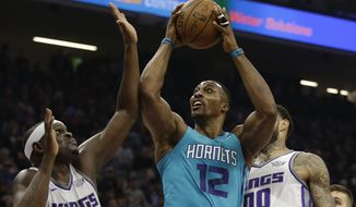 Charlotte Hornets center Dwight Howard , center, goes to the basket between Sacramento Kings' Zach Randolph, left, and Willie Cauley-Stein, right, during the first quarter of an NBA basketball game Tuesday, Jan. 2, 2018, in Sacramento, Calif. (AP Photo/Rich Pedroncelli)
