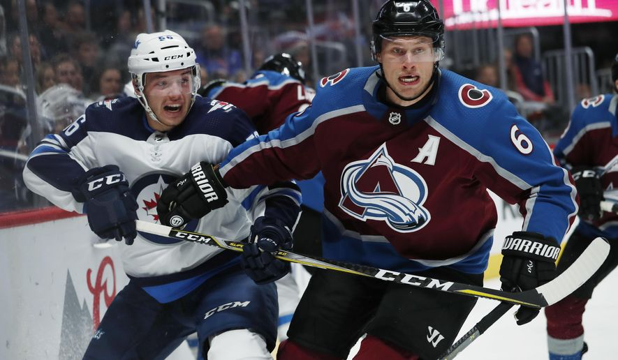 Colorado Avalanche defenseman Erik Johnson, right, checks Winnipeg Jets center Marko Dano, of Austria, as they pursue the puck in the second period of an NHL hockey game Tuesday, Jan. 2, 2018, in Denver. (AP Photo/David Zalubowski)