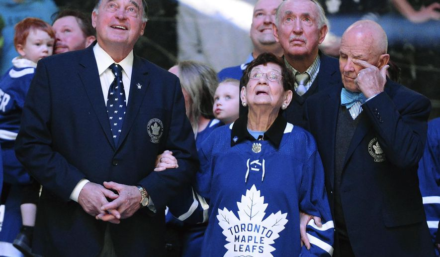 Nancy Bower, wife of the late NHL great Johnny Bower, watches a tribute to her husband with former Toronto Maple Leafs players Frank Mahovlich, left, and Dave Keon, right, prior to a hockey game between the Maple Leafs and the Tampa Bay Lightning on Tuesday, Jan. 2, 2018, in Toronto. (Frank Gunn/The Canadian Press via AP)