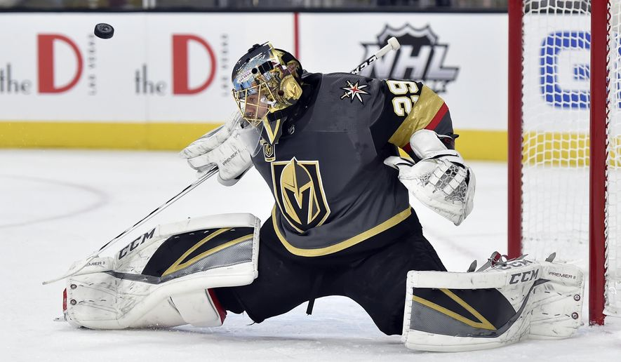 Vegas Golden Knights goalie Marc-Andre Fleury deflects the puck on a shot by the Nashville Predators during the first period of an NHL hockey game Tuesday, Jan. 2, 2018, in Las Vegas. (AP Photo/David Becker)