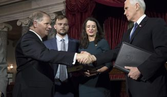 Vice President Mike Pence, right, shakes hands with Sen. Doug Jones, D-Ala., left, after administering the Senate oath of office during a mock swearing in ceremony in the Old Senate Chamber to Jones, with his wife Louise Jones, second from right, Wednesday, Jan. 3, 2018 on Capitol Hill in Washington.  They are joined by their son, Carson Jones, center.  Jones defeated Republican Roy Moore in a special election to take the seat once held by Attorney General Jeff Sessions.  (AP Photo/J. Scott Applewhite)