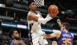 Denver Nuggets guard Gary Harris, center, goes up for a basket between Phoenix Suns guard Troy Daniels, left, and forward Dragan Bender, of Croatia, in the first half of an NBA basketball game Wednesday, Jan. 3, 2018, in Denver. (AP Photo/David Zalubowski)