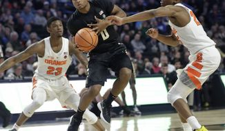 Wake Forest's Brandon Childress (0) drives between Syracuse's Frank Howard (23) and Tyus Battle (25) during the first half of an NCAA college basketball game in Winston-Salem, N.C., Wednesday, Jan. 3, 2018. (AP Photo/Chuck Burton)