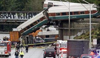 FILE - In this Dec. 18, 2017 file photo, cars from an Amtrak train lie spilled onto Interstate 5 below alongside smashed vehicles as some train cars remain on the tracks in DuPont, Wash. A conductor who was injured when a speeding Amtrak train flew off the tracks and onto a Washington state highway last month has filed a lawsuit Wednesday, Jan. 3, 2018, against the passenger rail company. Lawyers for Garrick Freeman of Bellevue, Wash., say Amtrak failed to provide a safe work environment. (AP Photo/Elaine Thompson, File)